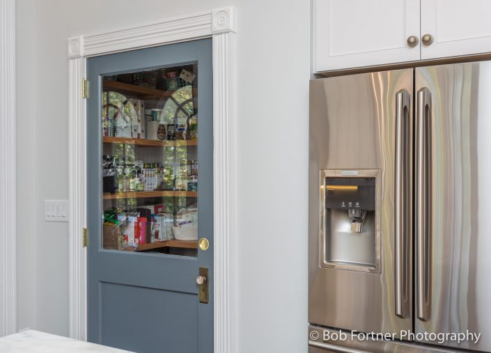 Custom, blue pantry door with glass.